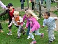 Przyjaciele w parku kotów - Zwyciężył pierwszy. Troszkę dziewczyna trzyma futbolową piłkę.