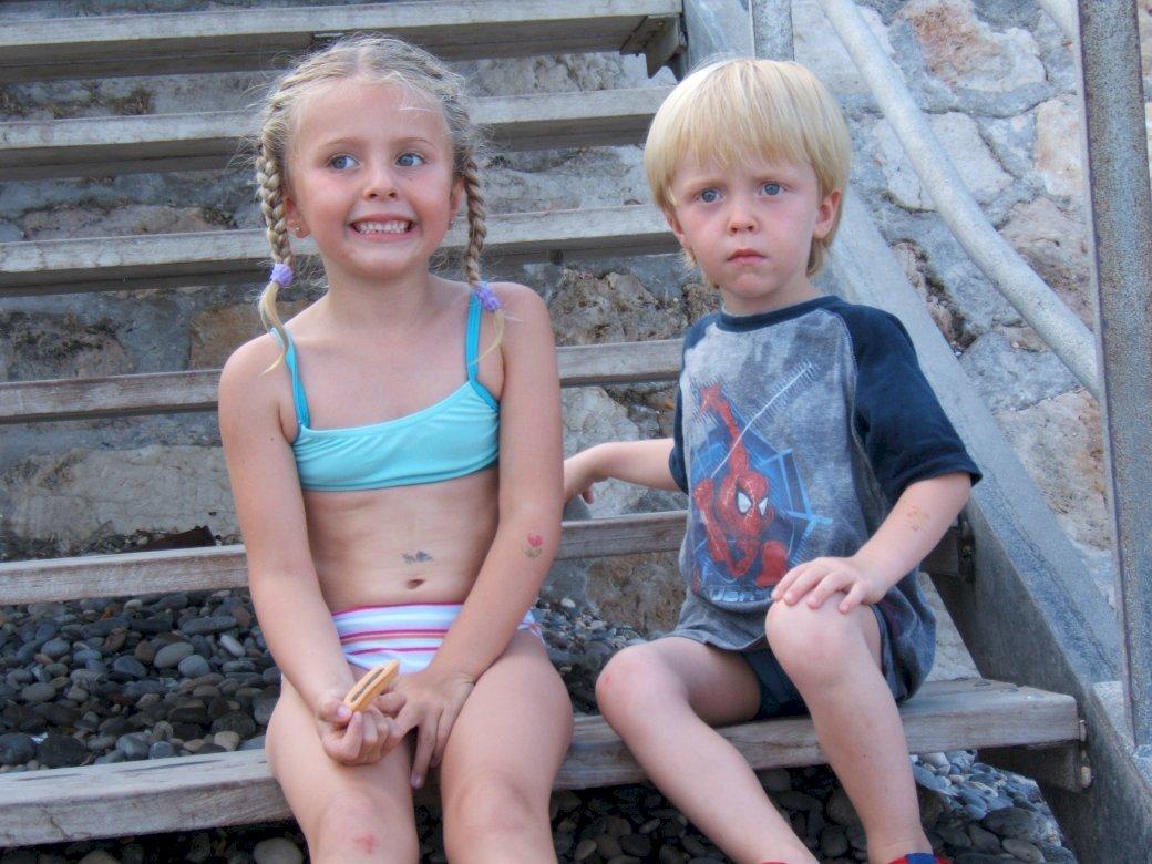 Lorna & Nathan - På stranden trappan. En liten flicka som sitter på en bänk (15×10)