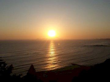 Solnedgång i Lima - Solnedgång, Lima, Peru. En solnedgång över en strand.