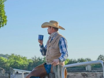 I went out to a ranch during - Man standing while holding blue cup. United States. A man wearing a hat.