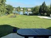 Annie fromi - Vista di santa livrade. Un paio di sedie da giardino seduto sulla cima di un campo coperto di erba.