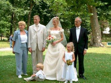 La famille au mariage - On est tous là sans exception !. Un groupe de personnes debout dans une robe de mariée.