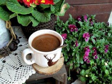 kawka z rana - kawa w otoczeniu kwiatów. Filiżanka kawy siedzi na górze kwiatu.
