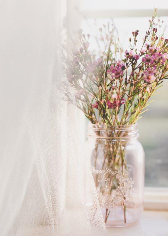 Fleurs roses - Fleurs roses dans un vase en verre rose. Un vase de fleurs sur une table (9×13)