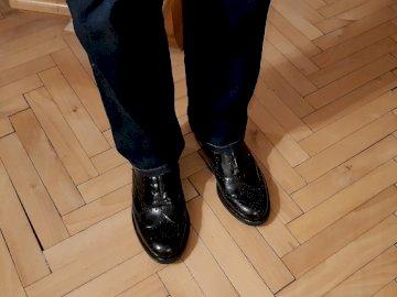 parquet viejo, zapatos viejos - antigua pista de baile, zapatos viejos y probablemente un anciano. Un par de piernas con zapatos neg