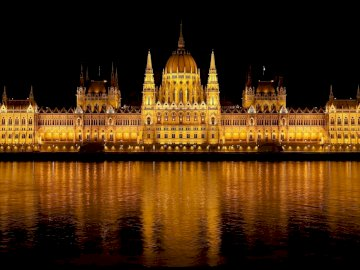 marie-do - Budapest illuminated at night in summer. A castle with a clock tower lit up at night with Hungarian