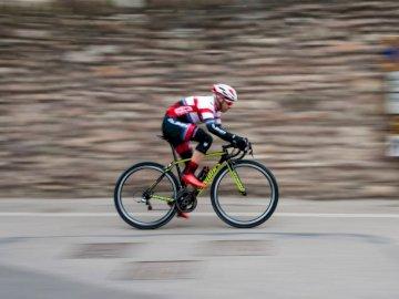 Speedy Bike - Mężczyzna jedzie zielonego i czarnego rower szosowego podczas dnia. Verona, Italia. Mężczyzna je