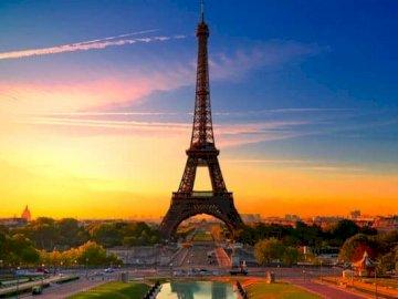 Wieża Eiffla - Krajobraz Paryża (Wieża Eiffla). Duża wieża z zachodem słońca w tle, z wieżą Eiffla w tle.