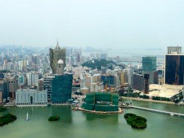 Vogelperspektive des Stadtzentrums von Macau - Luftaufnahme von Stadtgebäuden während des Tages. Macau. Ein kleines Boot in einem Gewässer mit e