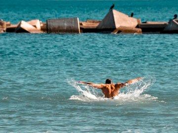 Pływanie i cieszenie się - Mężczyzna w błękitnych skrótach pływa w wodzie podczas dnia. Singapur. Osoba jadąca na desce