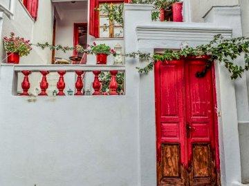 Grecia -------- - porta rossa -----------------. Una porta con un fiore rosso.