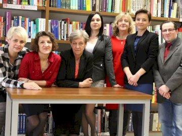 Bibliotekarze - Moje koleżanki i kolega bibliotekarze. Grupa ludzi pozujących do zdjęcia przed półką z książ