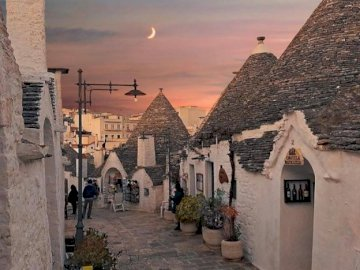 Alberobello, Italy - Unique stone huts in Alberobello, Italy. A stone castle next to a brick building.