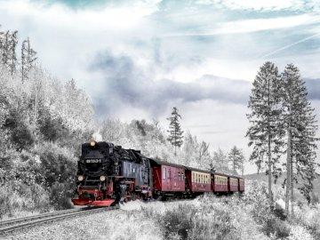 Zug auf einem schneebedeckten Berg - Zug auf einem schneebedeckten Berg. Ein Zug, der Bahngleise in der Nähe eines Waldes entlang fährt