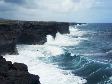 Litoral la Vulcani - Valurile se prăbușesc pe piatră. Germania. O insulă în mijlocul unui corp de apă.