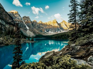 landscape - Moraine Lake, Canada. A close up of a hillside next to a body of water with Valley of the Ten Peaks