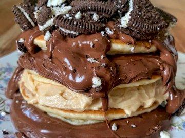 naleśniki Oreo - Naleśniki Nutella zwieńczone pokruszonymi ciasteczkami Oreo. Kawałek ciasta czekoladowe na talerz