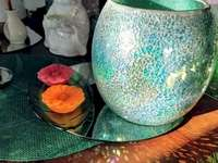 Partylite - Lampe tempête vert imperial. Un vase de fleurs sur une table.