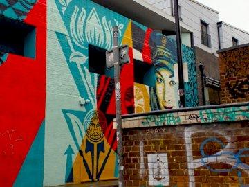 Street art, femme, rue - Lampe d'extérieur murale rouge et noire. Londres. Un bâtiment couvert de graffitis.