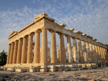 Acropolis monuments of Greece - Sights of Europe for class 1. GREECE. A large stone building with Parthenon in the background.