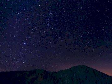 Étoiles, nature - Silhouette de montagnes sous la nuit étoilée. Macédoine. Une étoile dans le ciel.