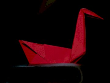 Origami, art - Red paper plane on black surface.