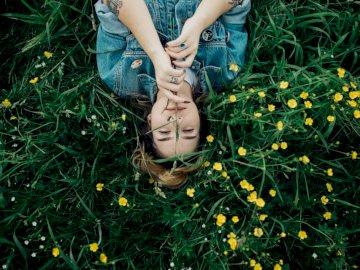 Αυτή η εικόνα τραβήχτηκε στο - Γυναίκα που βρίσκεται στο έδαφος χλόης με τα κίτρινα λ�