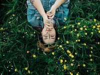 Esta imagem foi tirada no - Mulher deitada na grama moída com flores de pétalas amarelas. Charlotte, NC.