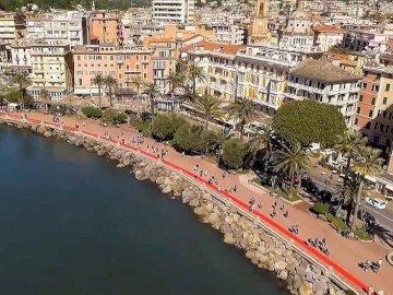 Italie - le plus long tapis - Le tapis rouge le plus long d'Italie. Un port avec des montagnes en arrière-plan.