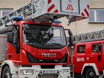 Straż pożarna - Ułóż obrazek ze strażą pożarną. Wóz strażacki jest zaparkowany z boku budynku.