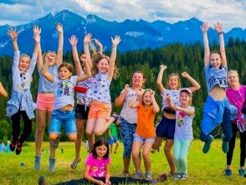 Le terrain est l'optimisme - amusant pour les enfants et les adultes. Un groupe de personnes posant pour une photo.