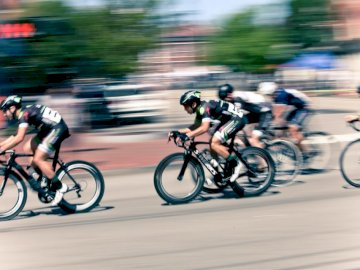 Annual Portsmouth Criterium. A - Time lapse photography of bikers. Boston. A man riding a bicycle down the street.