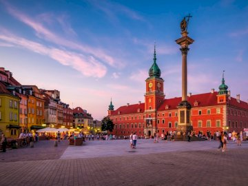 VARSOVIA, ZYGMUNT - VARSOVIA, REY ZYGMUNT, ESTATUA. Una pequeña torre del reloj en medio de la calle con el Castillo Re