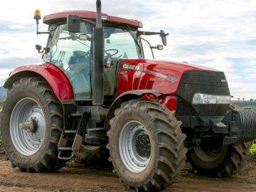 traktor case - znajdź wszystki puzzle. Duży ciągnik zaparkowany na ziemi.