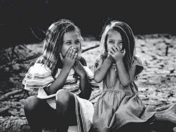 Las hermanas sonrientes - Fotografía en escala de grises de dos chicas cerrando la boca. Montpellier.