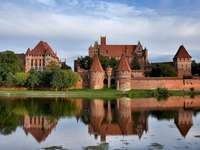 Castle in Malbork - Castle in Malbork. Teutonic Castle in Malbork. A castle on top of Malbork Castle surrounded by a bod