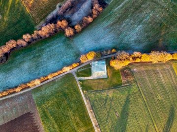 DJI drone shot - Aerial view of green field near body of water during daytime.