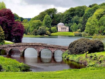 bridge_greens_construction - bridge_greens_construction. Stourhead over a body of water surrounded by trees.