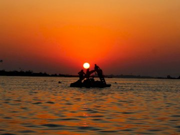 Sunset, vehicles - Silhouette of man riding on boat during sunset. egypt. A sunset over a body of water.