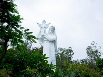 Statua Matki Boskiej z - Kobieta niosąca dziecko posąg betonowy. Melbourne. Wieża zegarowa przed drzewem.