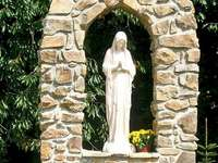Mary in the chapel - Mary in May in the chapel. A stone statue in front of a brick wall.