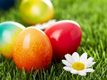Painted eggs - Eggs painted in Easter nature. A bowl of fruit sitting on top of a grass covered field.