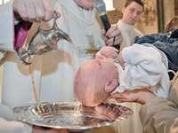 Taufe eines Kindes - sieben Sakramente - Taufe. Eine Person, die ein Glas Wein hält.