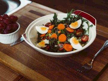 Salat zum Abendessen - Schüssel Salat mit Folie gekochtes Ei mit Trauben auf der Seite. Letchworth Garden City, Nord-Hertf