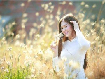 Wietnamska tradycyjna sukienka - Kobieta w białej koszuli z długim rękawem na polu zielonej trawie w ciągu dnia. Wietnam. Kobieta