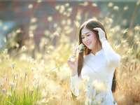 Vestido tradicional do Vietnã - Mulher de camisa branca de manga longa no campo de grama verde durante o dia. Vietnã. Uma mulher em
