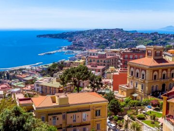 Italia - Bella Napoli - Italia-Napoli bellissima. Una vista di una città accanto a uno specchio d'acqua.