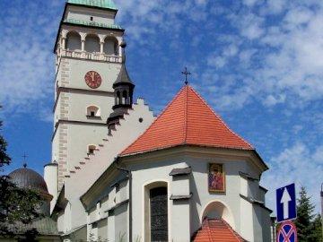Catedral de wywiec - la foto muestra una vista de la catedral de Żywiec. Una pequeña torre del reloj frente a una casa.