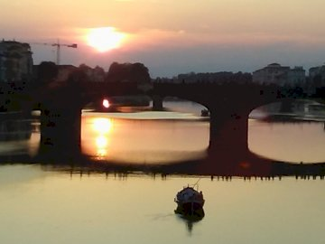 SUNSET IN FLORENCE - BRIDGE OVER RIO ARNO, FLORENCE. A sunset over a body of water.