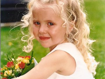 Lorna Berger - The wedding day at Parc Lefèvre. A little girl smiling at the camera. At Parc Lefèvre on the day o